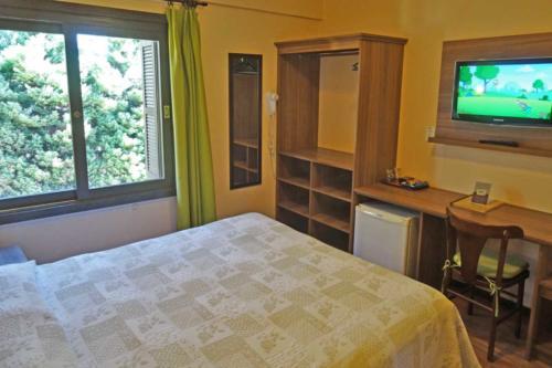 Suite Standard tv, armário e mesa.
